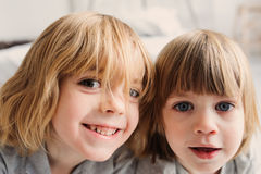 Two happy sibling boys playing together at home with toy cars Royalty Free Stock Photo