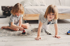 Two happy sibling boys playing together at home with toy cars Stock Images