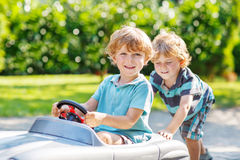 Two happy sibling boys playing with toy car Royalty Free Stock Photos