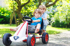 Two happy sibling boys playing with toy car Stock Photography