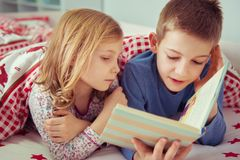 Two happy sibling children reading book in bunk bed under blanke. T Stock Photography