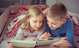 Two happy sibling children reading book in bunk bed under blanke. T Royalty Free Stock Photos