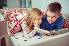 Two happy sibling children reading book in bunk bed under blanke. T Royalty Free Stock Image