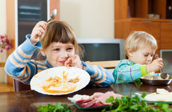 Two happy siblings eating food together Stock Images