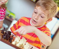 Two happy siblings playing chess Stock Photo