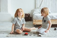 Two happy siblings playing with toy cars at home in the morning Stock Photos