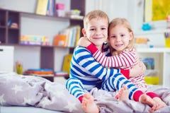 Two happy siblings in sleepwears in bed Royalty Free Stock Photos