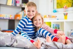 Two happy siblings in sleepwears in bed Royalty Free Stock Images