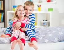 Two happy siblings in sleepwears in bed Stock Photos