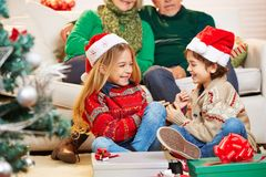 Siblings tickle each other at christmas. Two happy siblings tickle each other at christmas eve Stock Photography