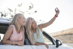 Two happy sister in car happy and smiling after shopping taking. Selfie stock image