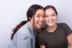 Two happy sisters on gray background. Smiling and laughing at the camera Royalty Free Stock Image