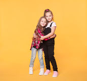Two happy sisters hugging isolated on yellow color background. Little kid girl embracing each other. Best friends in Trendy casual clothes stock photo
