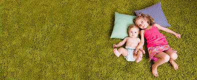Two happy sisters lie on carpet. Two sisters lie on green carpet and pillows. Top view. Empty space Royalty Free Stock Photos