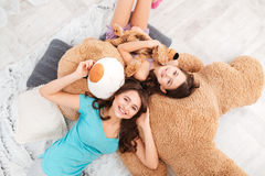 Two happy sisters lying on huge plush bear and laughing Stock Photos