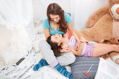 Two happy sisters lying and talking in children room Royalty Free Stock Photos