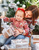 Two happy sisters opening Christmas presents Royalty Free Stock Image