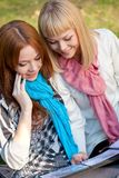 Two happy sisters with photo album in the park Royalty Free Stock Photo