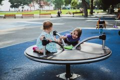 Two happy sisters playing on the children's playground on the carousel. Kids always like to turn quickly. stock image