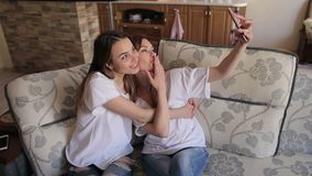 Portrait of two girls taking selfies on the couch. Two happy sisters in the same white t-shirts take a selfie sitting on the couch at home. Portrait of two stock video