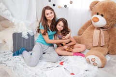 Two happy sisters sitting and hugging in children room Stock Image