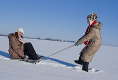 Two happy sisters sledding. At winter time Stock Photos