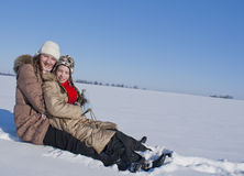 Two happy sisters sledding. At winter time Stock Photo