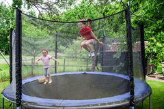 Two happy sisters on trampoline. Children leisure royalty free stock images