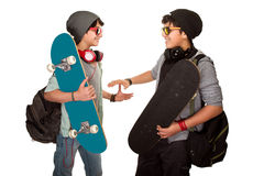 Two happy skateboarders. Acclaiming each other isolated on white background, best friends wearing stylish hats, sunglasses and listening music from earphone Royalty Free Stock Photo
