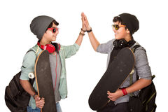 Two happy skateboarders. Acclaiming each other isolated on white background, best friends wearing stylish hats, sunglasses and listening music from earphone Stock Image
