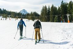 Two happy skiers go to the ski lift on a winter day. stock photo