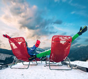 Two happy skiers have a relax time in red chairs on top of mountain Stock Images