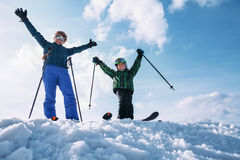 Two happy skiers stay together on the top of snow hill Stock Photos