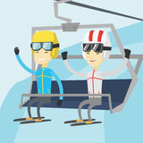 Two happy skiers using cableway at ski resort. Stock Photos