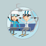 Two happy skiers using cableway at ski resort. Royalty Free Stock Images