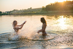 Two happy slim young girls splashing in lake at Royalty Free Stock Photography