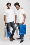 Two happy smart young boys posing with shopping bags Royalty Free Stock Image