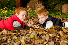 Two happy and smiling brothers lying in a pile of Stock Image