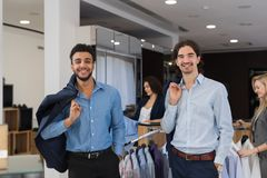 Two Happy Smiling Businessmen Wearing Elegant Suits Standing In Modern Menswear Retail Store. Successful Business Men Buy New Clothes Royalty Free Stock Photography
