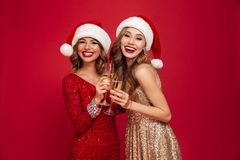 Two happy smiling girls in christmas hats. Toasting with champagne glasses and looking at camera isolated over red background Royalty Free Stock Photos