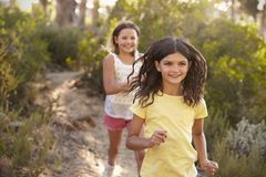 Two happy smiling girls running after each other in a forest Royalty Free Stock Photos