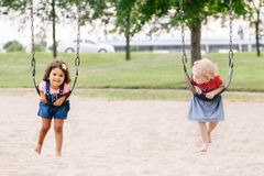 Two happy smiling little toddlers girls friends swinging on swings at playground outside. Portrait of two happy smiling little toddlers girls friends swinging on stock photos