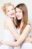 Two happy smiling women friends embracing and smiling in studio Stock Image