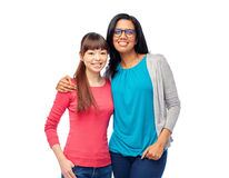 Two happy smiling women or international friends. Diversity, race, ethnicity and people concept - two happy smiling women or international friends Royalty Free Stock Images