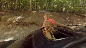 Two happy smiling young blondes waving their hands out of the hatch of a car on the move against the forest. HD stock video footage