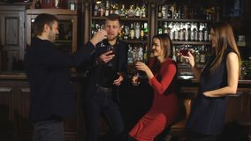 Two happy smiling young couples with champagne at celebration. Party or romantic date at club stock footage