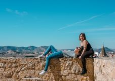 Women embrace and laugh while sitting on the castle stone. Two happy smiling young people friends outdoor. Two women on the castle stone stock photos