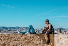 Women embrace and laugh while sitting on the castle stone stock photography