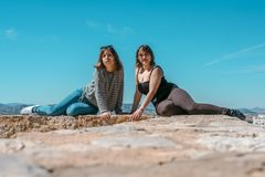 Women embrace and laugh while sitting on the castle stone stock image