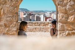 Women embrace and laugh while sitting on the castle stone. Two happy smiling young people friends outdoor. Two women on the castle stone royalty free stock photography